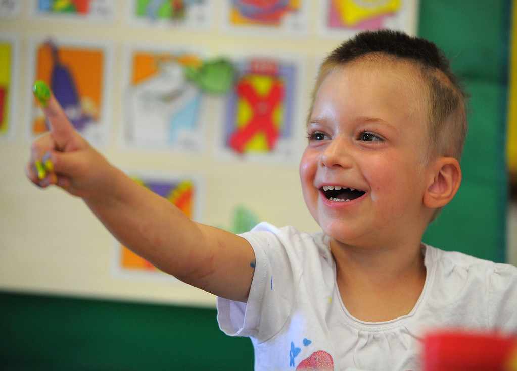 . Pre-schooler Nicole Intagliata laughs as she holds up a finger covered in paint during class at Buffum Total Learning Center in Long Beach, CA on Wednesday, October 9, 2013.  Beginning next week, Buffum, a pre-school for special needs students, will start a program called Typical Peers which will have their students with disabilities working side by side with normally developing students. (Photo by Scott Varley, Daily Breeze)