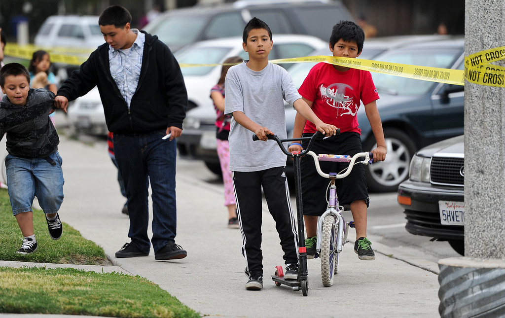Description of . Children loiter near a crime scene while police investigate the scene of a double homicide on the 300 block of Orchid Lane in Pomonaon Saturday, April 13, 2013. Two teenagers, a 16-year-old and 13-year-old boy, were fatally shot and one adult male was critically wounded, according to authorities. (Rachel Luna / Staff Photographer)