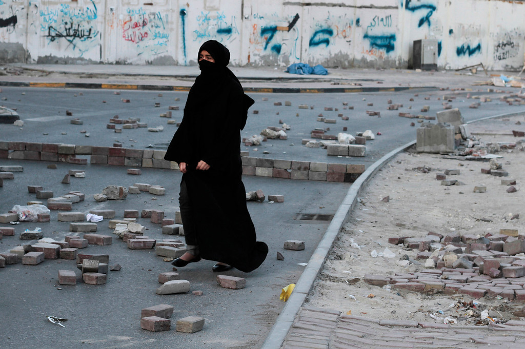 . A Bahraini anti-government protester walks on a street filled with bricks meant to slow down riot police vehicles during clashes in Manama, Bahrain, Monday, Feb. 25, 2013. Protesters tried from several directions to reach the country\'s main public hospital, which is heavily guarded, to forcibly claim for burial the body of a 20-year-old who died Thursday from injuries sustained during earlier clashes with police. (AP Photo/Hasan Jamali)