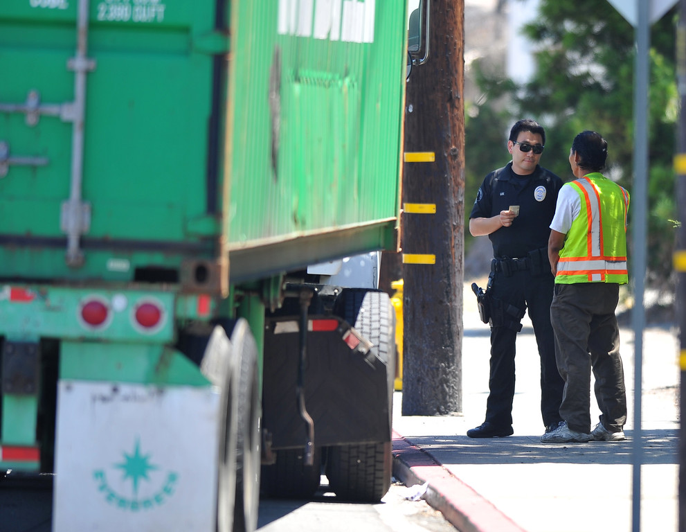 . An L.A. Port police officer gives a warning to a truck driver who, after being delayed from leaving the Evergreen terminal, made an unsafe move by turning towards the picketers on Terminal Island, CA on Wednesday, July 9, 2014. (Photo by Scott Varley, Daily Breeze)