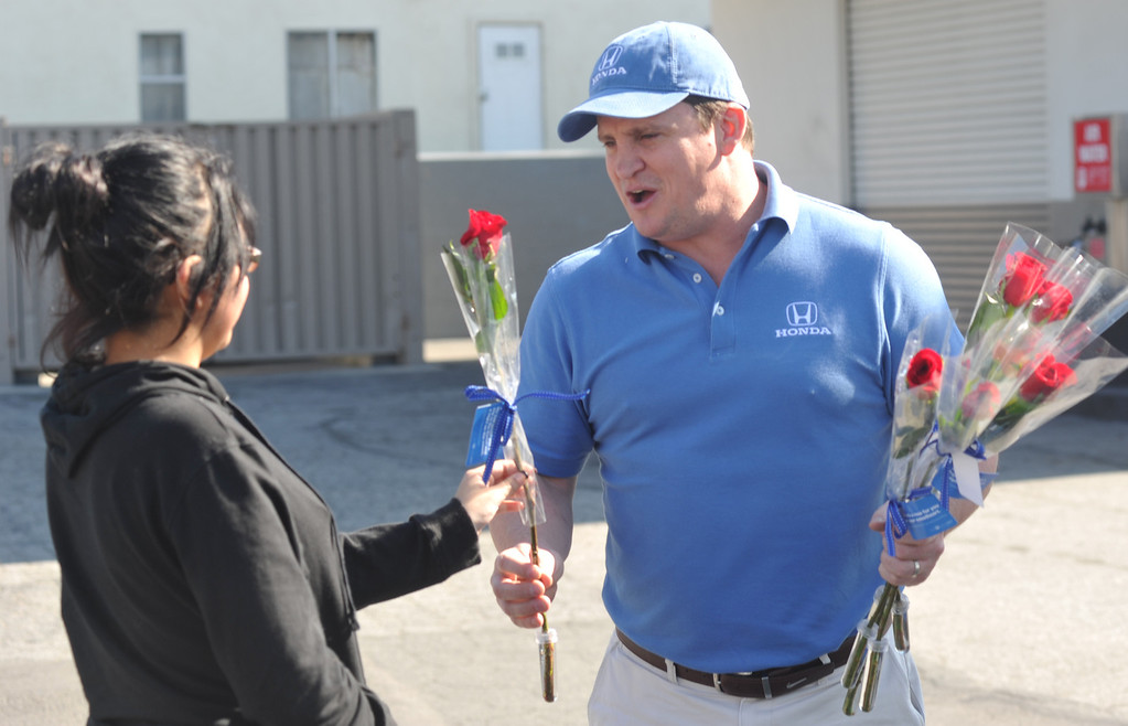 Description of . Steve Judkins, with Honda, gives Jazal Ibanez a long-stem red rose on Valentine's Day at Merill Gardens in Whittier on Thursday February 14, 2013. The Helpful Guys in Blue, a group sponsored by the Southern California Honda Dealers Association surprise Whittier residents with a complimentary red roses. (SGVN/Staff Photo by Keith Durflinger)