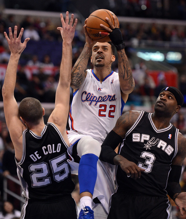 . The Clippers\' Matt Barnes #22 drives between Spurs\' Nando de Colo #25 and Stephen Jackson #3 to the hoop during their game at the Staples Center in Los Angeles Friday, February  21, 2013. The Spurs beat the Clippers 116-90. (Hans Gutknecht/Staff Photographer)