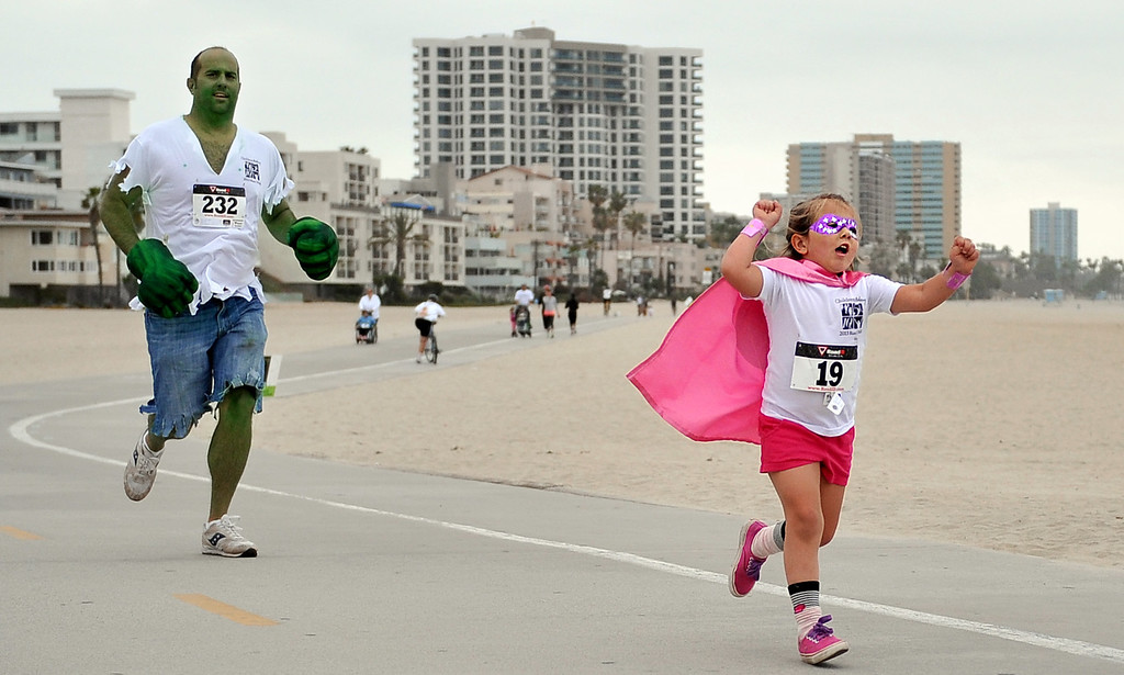 . 5/25/13 - Super hero Harper Macy, 4, finishing the 1-mile fun run with her hulk of a dad, Chris Macy supporting her, during the Children Today\'s 5th Annual run/walk at Marina Green Park. The local non-profit, Children Today, is an organization that provides for families and children experiencing homelessness in Long Beach. They\'ve raised $33,184 and their final goal is $50,000. Photo by Brittany Murray / Staff Photographer