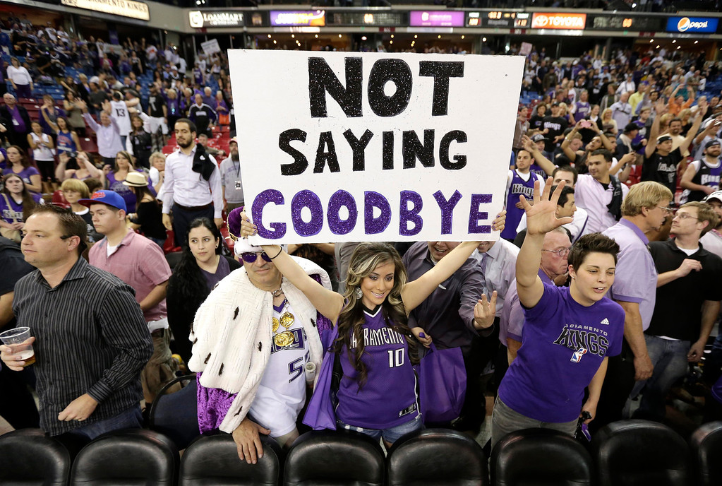 . Adriana Ortiz, center, holds up a sign expressing her hopes that the team won\'t move after the Kings 112-108 loss to the Los Angeles Clippers in an NBA basketball game in Sacramento, Calif., Wednesday,  April 17, 2013.  With the pending sale of the team and possible move to Seattle, Wednesday\'s game might be the last in Sacramento.(AP Photo/Rich Pedroncelli)