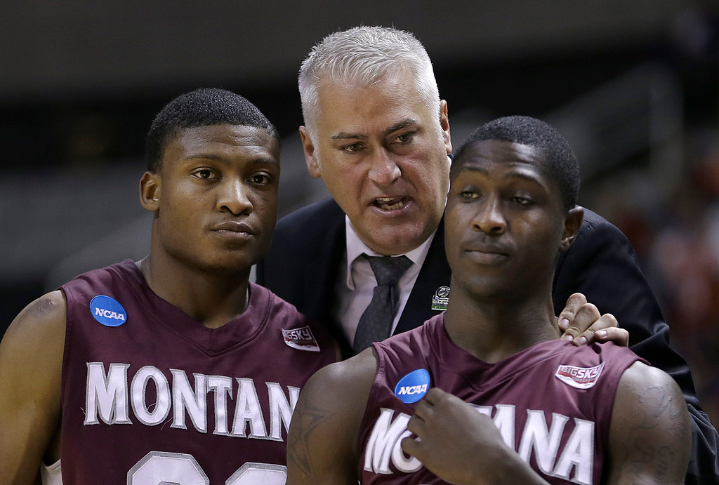 . Montana head coach Wayne Tinkle, center, talks with Kareem Jamar, left, and Will Cherry during the second half of a second-round game in the NCAA college basketball tournament against Syracuse in San Jose, Calif., Thursday, March 21, 2013. Syracuse won 81-34. (AP Photo/Ben Margot)