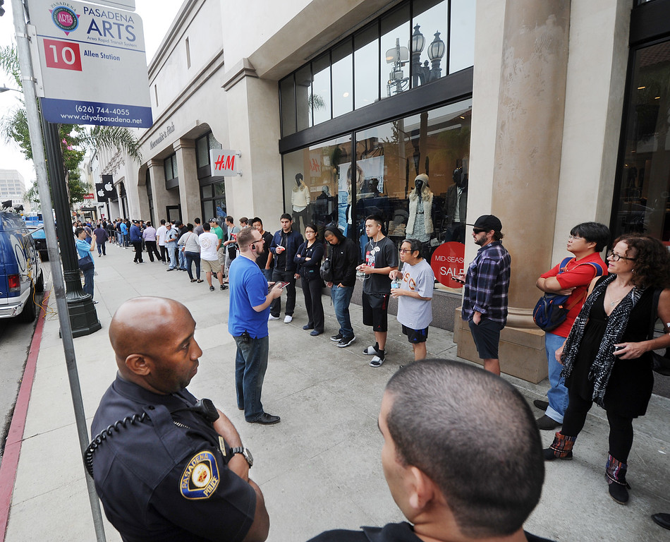 . Apple saleman talks to the crowd waiting to purchase new IPhones at Apple Store in Pasadena Friday, September 20, 2013. Police detained three people after a fight erupted outside Apple Store,where a crowd waited overnight for release of the new iPhone. The fight was over homeless people who were promised $40 and didn\'t get paid, to wait overnight to purchase IPhones for a buyer.(Photos by Walt Mancini/Pasadena Star-News)