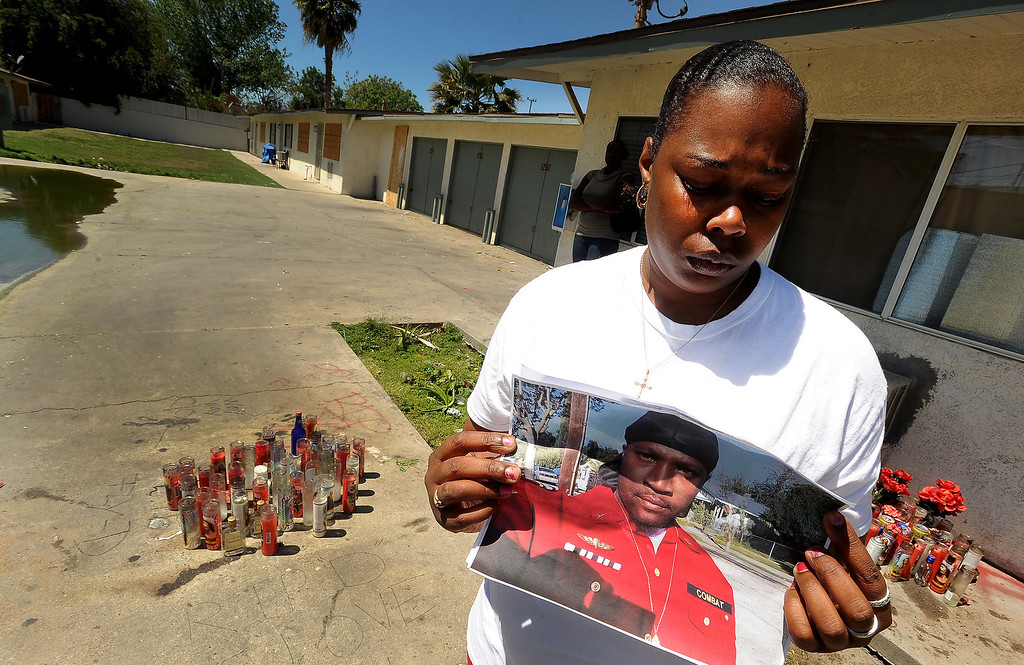 ". Ganesha Boone, 35, holds a picture of boyfriend Jerald Lee Belton at a memorial site along North Sierra Way in San Bernardino April 18, 2013.  ""He was taken away too soon,\"" said Boone. \""There are so many people that\'s hurting behind losing him.\"" GABRIEL LUIS ACOSTA/STAFF PHOTOGRAPHER."