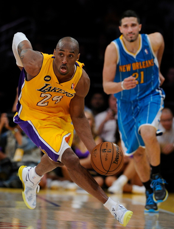 . Lakers#24 Kobe Bryant picks up a loose ball in front of Hornets#21 Greivis Vasquez in the 4th quarter. The Lakers defeated New Orleans Hornets 104-96 in a game played at Staples Center in Los Angeles, CA 4/9/2013(John McCoy/Staff Photographer