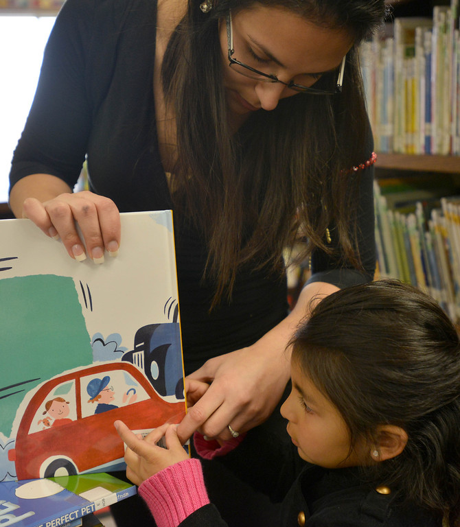 . 03-16-2013--(LANG Staff Photo by Sean Hiller)- Volunteers and students help the Anderson Elementary School Library sort and process new and donated books as well as spiff up campus with some colorful murals at Saturday\'s event organized by Access Books. Julie Tellez and daughter Katelynn,5, help to process new books at the school library.