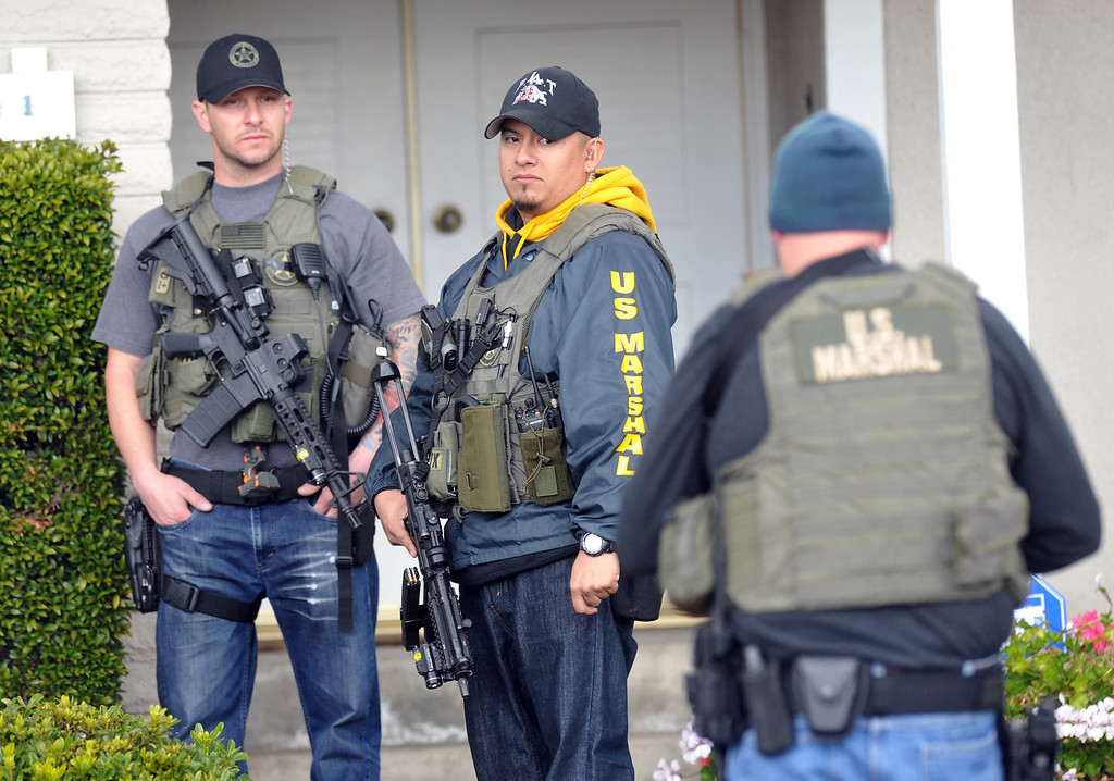 . U.S. Marshals and La Palma  Police stand weapons ready outside of what is believed to be Christopher Dorner\'s mother\'s La Palma home as FBI computer recovery task force investigators armed with a search warrant go through a computer on Friday February 8, 2013. Various agencies have arrived to lend assistance at the home. (SGVN/Staff Photo by Keith Durflinger)
