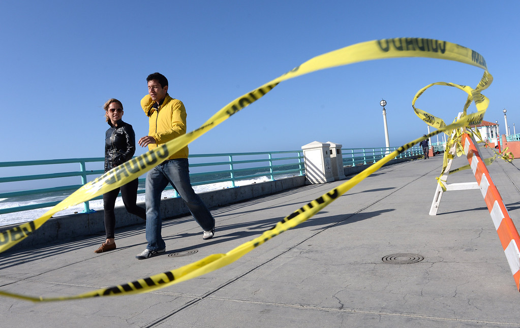 . High winds came to the southland today. Here a couple walk on the Manhattan Beach Pier Monday 4-8-13. Photo by Brad Graverson