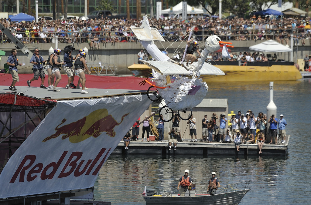 ". LONG BEACH, CALIF. USA -- Brett Hileman pilots ""Unexpected Delivery\"" during the Flugtag in Rainbow Harbor in Long Beach, Calif. on August 21, 2010. Thirty five teams competed in the Red Bull event where teams build homemade, human-powered flying machines and pilot them off a 30-foot high deck in hopes of achieving flight.  Flugtag means \""flying day\"" in German. They are on distance, creativity and showmanship..Photo by Jeff Gritchen / Long Beach Press-Telegram.."