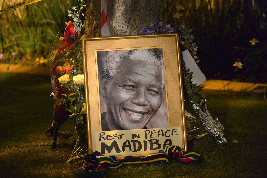 . This picture shows a framed image of former South African president Nelson Mandela as people pay tributes following his death, in Johannesburg on December 6, 2013. Nelson Mandela, the revered icon of South Africa\'s anti-apartheid struggle and a towering figure of 20th century politics, died on December 5 aged 95.          (ALEXANDER JOE/AFP/Getty Images)