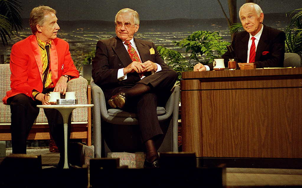". Talk show host Johnny Carson, behind his desk, Doc Severinsen, left, leader of ""The Tonight Show Band\"", and announcer Ed McMahon, center, share some moments together during the final taping of the \""Tonight Show\"" in Burbank, Ca., Friday, May 22, 1992.  (AP Photo/Douglas C. Pizac)"