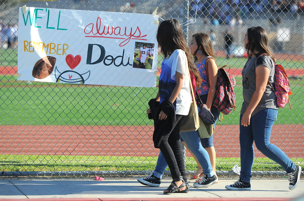 . Downey High students leaving school Thursday walk past a banner honoring 16-year-old Dodi Soza in Downey, CA on Thursday, October 17, 2013. Dodi Soza collapsed on the field after scoring a touchdown and died two days later on Saturday.  (Photo by Scott Varley, Daily Breeze)