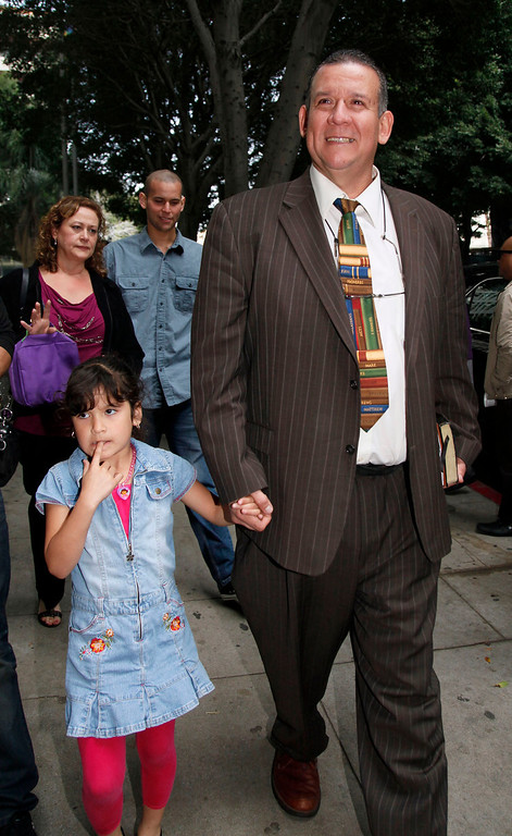. Former Councilman Luis Artiga leaves court after celebrating his acquittal, with his daughter, Sarah Artiga, 7, after the Bell trial verdicts were read Wednesday March 20, 2013 in Los Angeles. Five former elected officials of the tiny California city of Bell were convicted Wednesday of multiple counts of misappropriation of public funds, and a sixth defendant, Artiga, was cleared entirely. (AP Photo/Nick Ut)