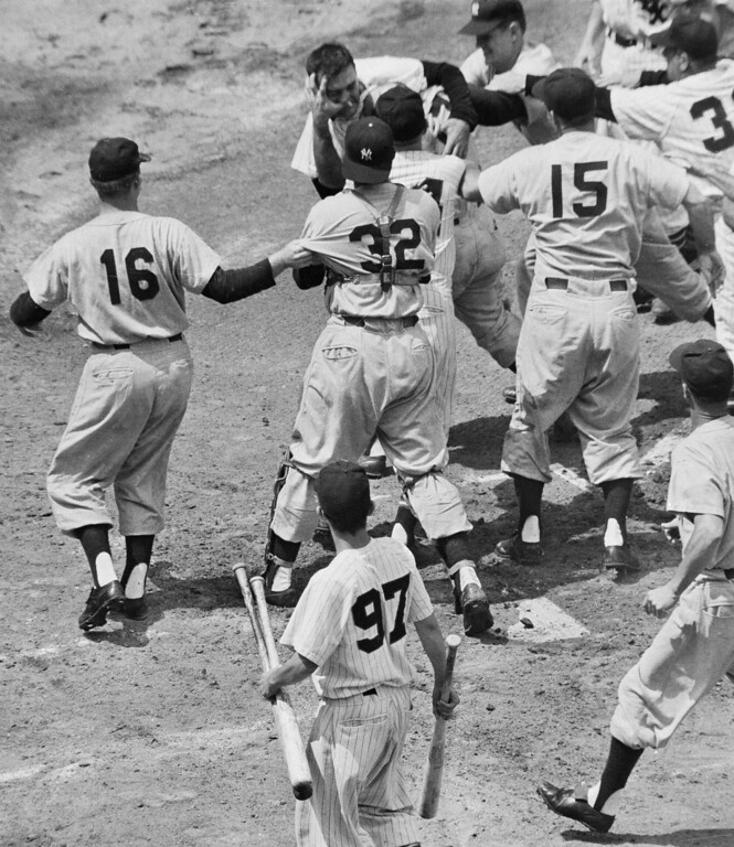 . Walt Dropo (hatless) of the Chicago White Sox has his face grabbed by the New York Yankees Enos Slaughter in the first inning of their game in Chicago, June 13, 1957. Yankees catcher Elston Howard (32) and Sox coach Johnny Cooney (in front of Howard) try to break it up, along with teammates. (AP Photo/Harry Hall)
