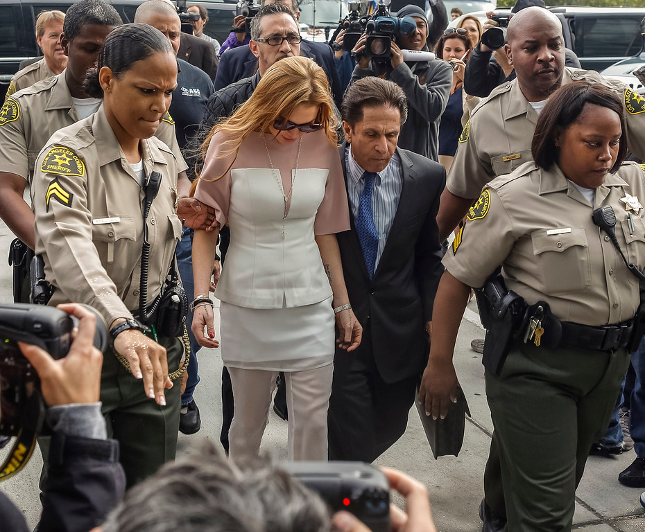 . Actress Lindsay Lohan is escorted by Los Angeles County sheriffs as she arrives for her trial with her attorney Mark Heller, on Monday, March 18, 2013. Lohan is charged with three misdemeanor counts stemming from a crash on Pacific Coast Highway. She is charged with willfully resisting, obstructing or delaying an officer, providing false information to an officer and reckless driving. She is also accused of violating her probation in a misdemeanor jewelry theft case. (AP Photo/Damian Dovarganes)