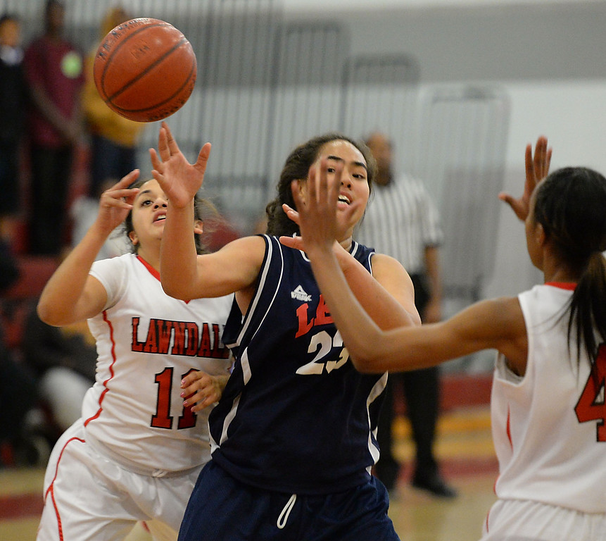 . Lawndale\'s Roxanne Gorostieta (11) and Taylor Hall (4) battle Leuzinger\'s Taiana Puloka (23) in a girls basketball game at Lawndale High Tuesday, December 10, 2013, in Lawndale, CA.  Photo by Steve McCrank/DailyBreeze