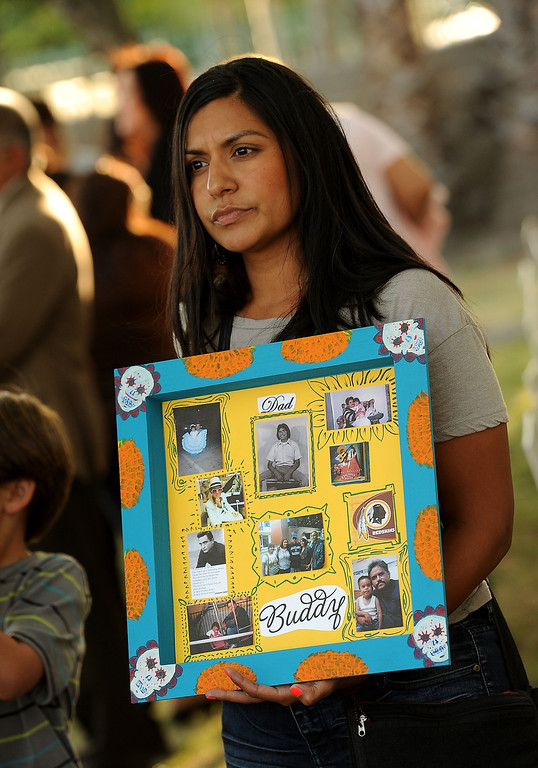 Description of . Angelina Martinez, 29, holds a photo collage of her father Christopher Martinez during the annual Victims Candlelight Vigil at the police station in San Bernardino April 23, 2013.  Martinez was shot and killed March 28, 2012 along Highland Avenue in San Bernardino.  GABRIEL LUIS ACOSTA/STAFF PHOTOGRAPHER.