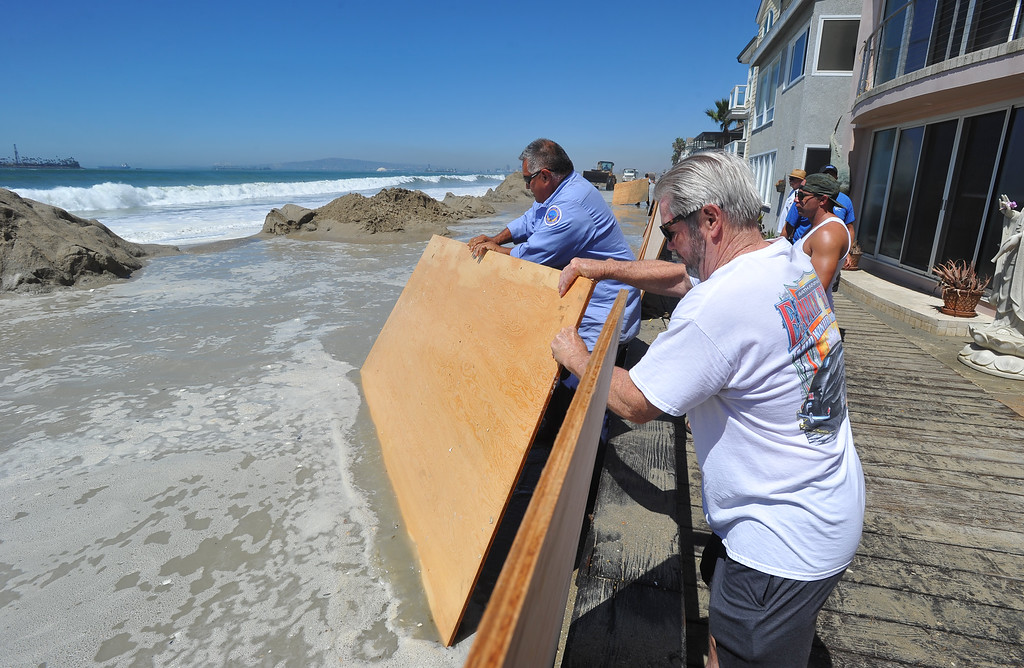 Description of . Plywood sheets are placed against a wall to try to stop water from splashing over as high tide and a storm surge from Hurricane Marie had locals bracing for the worst in the Peninsula neighborhood in Long Beach, CA on Wednesday, August 27, 2014. With city crews constantly building a sand berm, the water was held back from the homes and streets during the morning high tide. (Photo by Scott Varley, Daily Breeze)