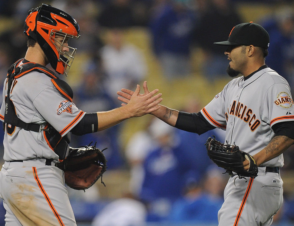 . San Francisco Giants relief pitcher Sergio Romo shakes hands with catcher Buster Posey after defeating the Los Angeles Dodgers 5-3 during their baseball game against the Los Angeles Dodgers on Wednesday, April 3, 2013 in Los Angeles. 