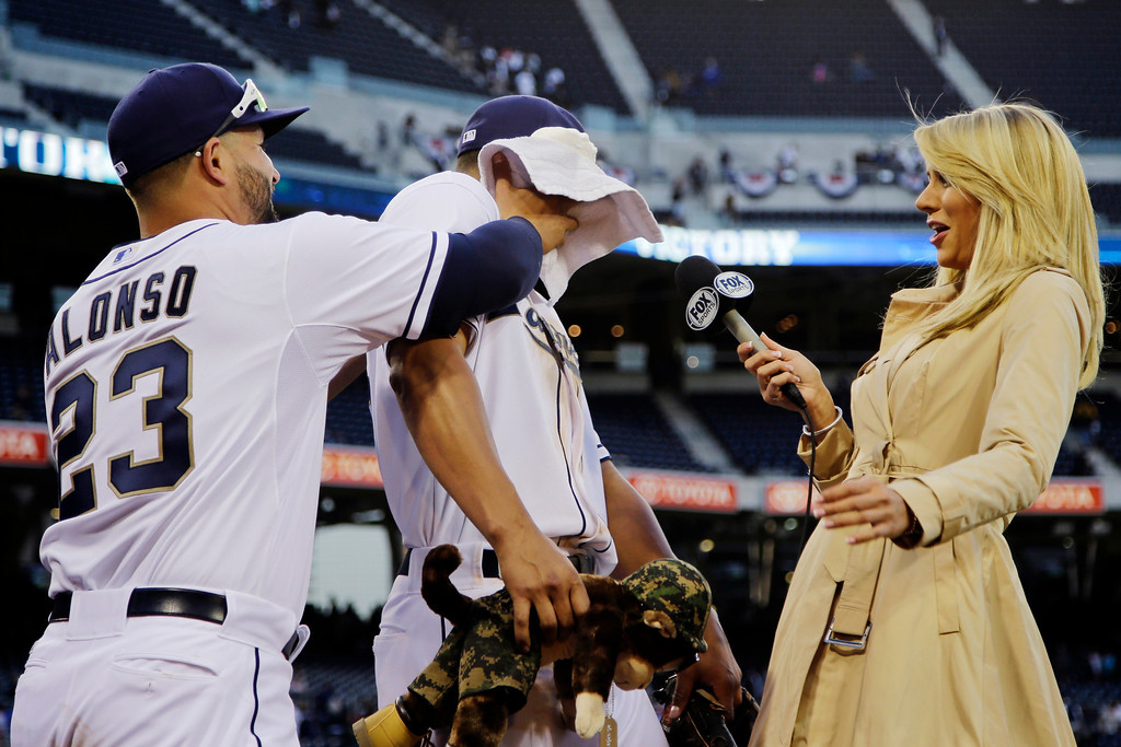 . San Diego Padres\' Will Venable gets a face full of shaving crew from teammate Yonder Alonso while being interviewed by   reporter Laura McKeeman following their 9-3 win over the Los Angeles Dodgers in a baseball game in San Diego, Tuesday, April 9, 2013. (AP Photo/Lenny Ignelzi)