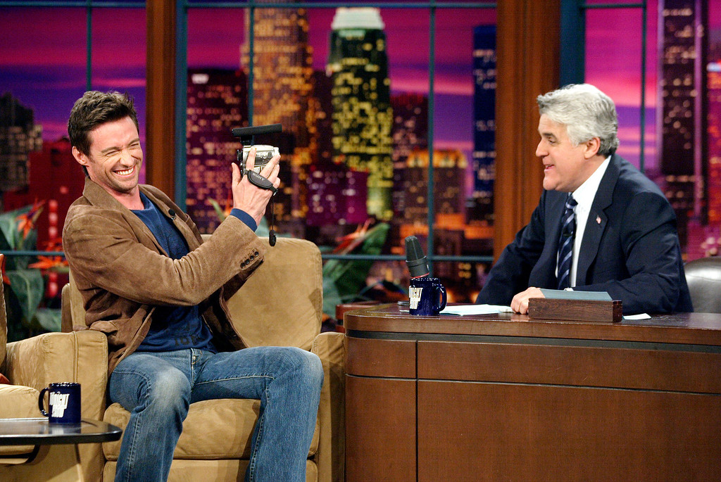 """. In this photo released by NBC, Australian actor Hugh Jackman rolls a video camera and asks \""""Tonight Show\"""" host Jay Leno, the band and the studio audience to tape a birthday greeting for Jackman\'s father during his visit to the show at NBC studios in Burbank, Calif., Friday, April 28, 2006. Jackman also promoted his upcoming X-Men film, and joked with Leno about beating him out for the Emmy. (AP Photo/NBC, Paul Drinkwater) ** NO SALES **"""