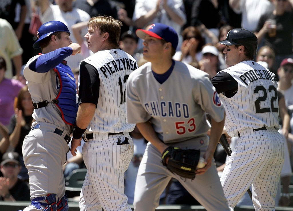 . Chicago Cubs catcher Michael Barrett, left, scuffles with Chicago White Sox\'s A.J Pierzynski after a collision between the two at home plate as White Sox\'s Scott Podsednik (22) comes in to break up the scuffle during the second inning of a baseball game, Saturday, May 20, 2006, in Chicago. The scuffle set off a bench-clearing brawl. Cubs pitcher Rich Hill stands at front. (AP Photo/Jeff Roberson)