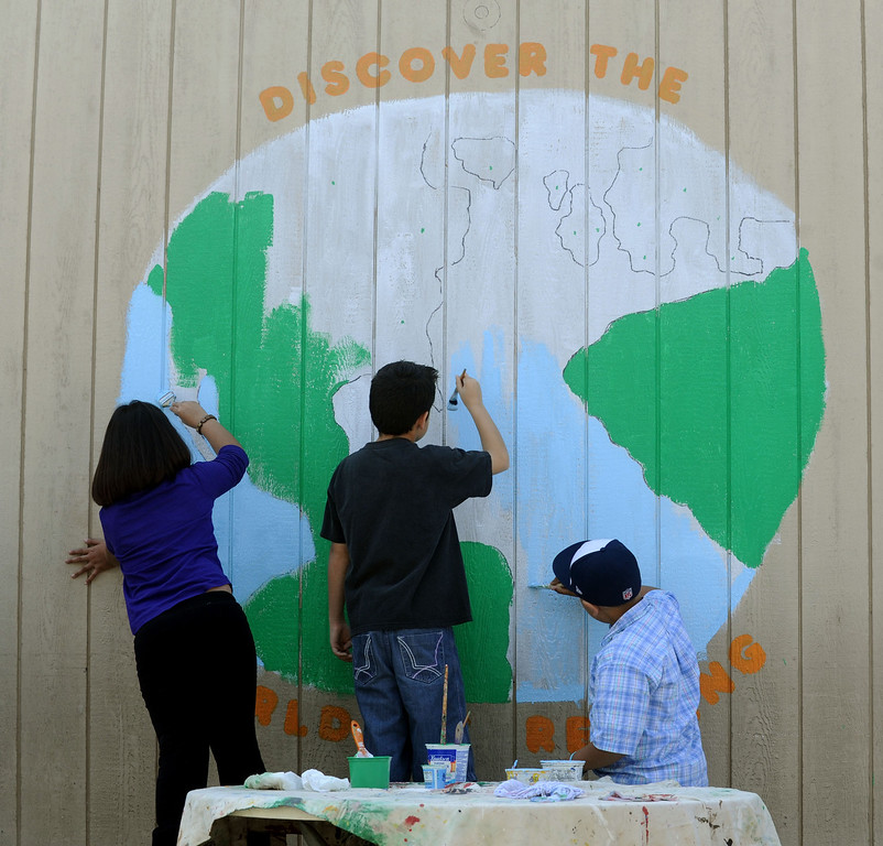 . 03-16-2013--(LANG Staff Photo by Sean Hiller)- Volunteers and students the help Anderson Elementary School Library sort and process new and donated books as well as spiff up campus with some colorful murals, like this one of the world, at Saturday\'s event organized by Access Books.