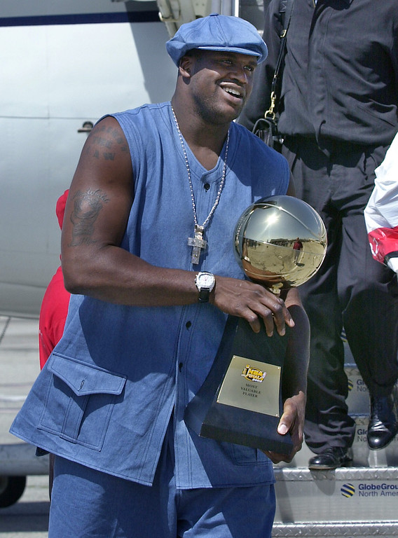 . The Los Angeles Lakers\' Shaquille O\'Neal carries his series MVP trophy as the winners of the NBA Finals arrive from New Jersey at Los Angeles International Airport Thursday, June 13, 2002.  The Lakers swept the New Jersey Nets 4-0 to take their third consecutive NBA Championship. (AP Photo/Nick Ut)