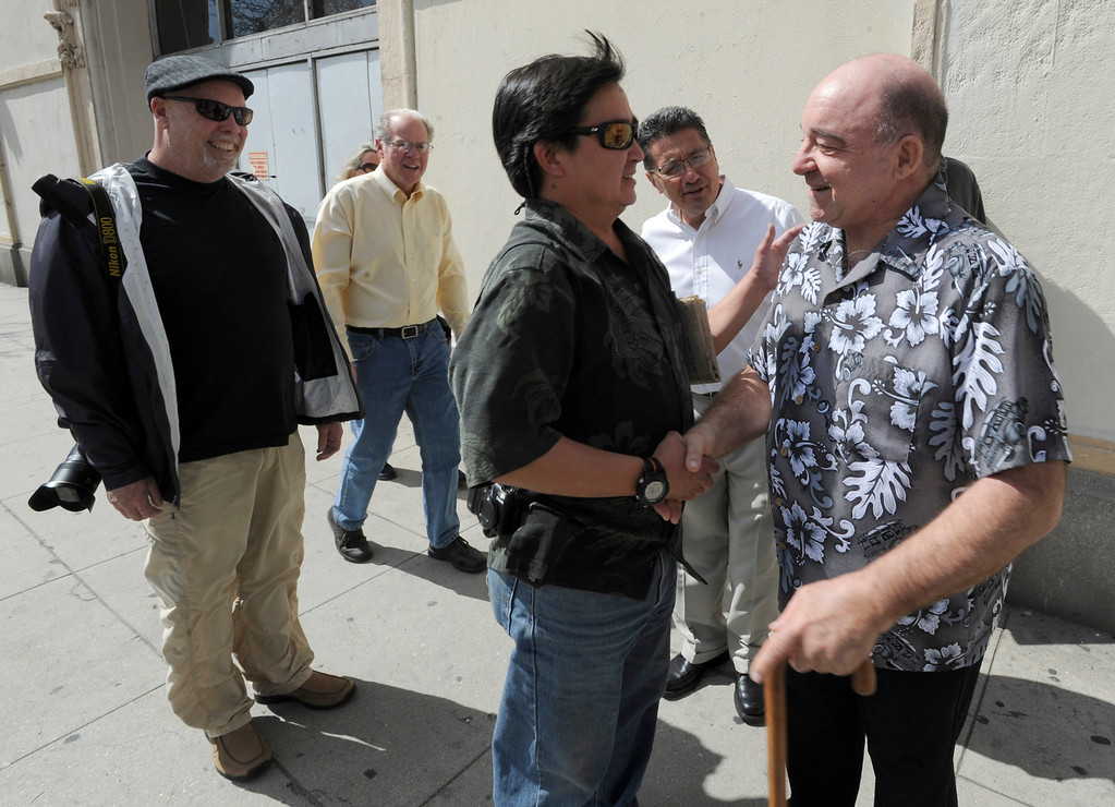 . (l-r) Mike Jacobs, Jim Ruebsamen and Javier Mendoza look on as Paul Chin shakes hands with Guy Goodenow in front of the Herald building. Former photographers from the Los Angeles Herald Examiner  gathered to take a tour of the old Herald Building, and then joined for a panel discussion about their work and their days working at the old Herex. Los Angeles, CA 3/9/2013(John McCoy/Staff Photographer)