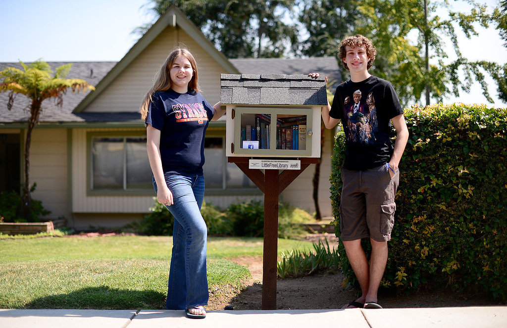 . Stephanie Cox, 18, who created five free book nooks in Monrovia for her Girl Scout Gold Award Project, poses with her friend Travis Stone, 18, at her home\'s free library on Scenic Drive. Stone helped Cox with the project and runs the Facebook page. (SGVN/Staff Photo by Sarah Reingewirtz)