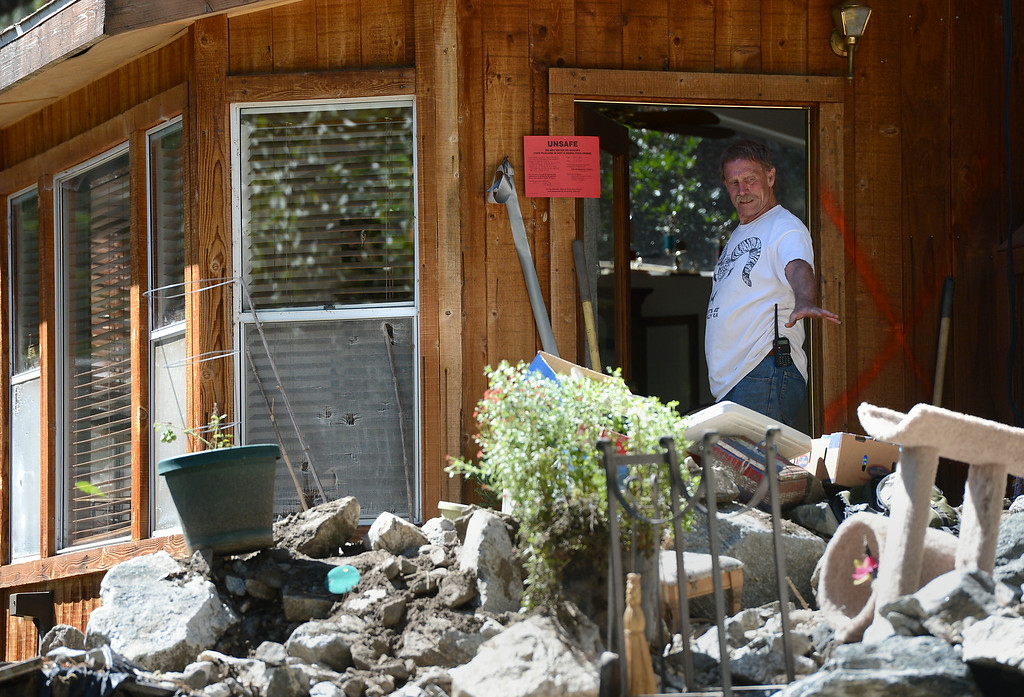 Description of . Eric Olson stands in the doorway of his red-tagged home while trying to clean-up from Sunday's storm in Mt. Baldy, CA, Tuesday, August 5, 2014. (Photo by Jennifer Cappuccio Maher/Inland Valley Daily Bulletin)