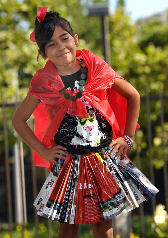 Description of . Jazmin Ramon, 8, shows her plastic store bag blouse and pleated skirt made of magazine pages in the
