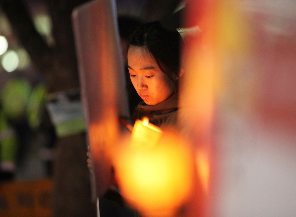 . A protester holds a candle during a rally denouncing the annual Foal Eagle, South Korea and the United States joint military exercise, near the U.S. embassy in Seoul, South Korea, Friday, April 5, 2013.  North Korea has been railing against U.S.-South Korean military exercises that began in March and are to continue until the end of this month. The allies insist the exercises in South Korea are routine, but the North calls them rehearsals for an invasion and says it needs nuclear weapons to defend itself. (AP Photo/Ahn Young-joon)