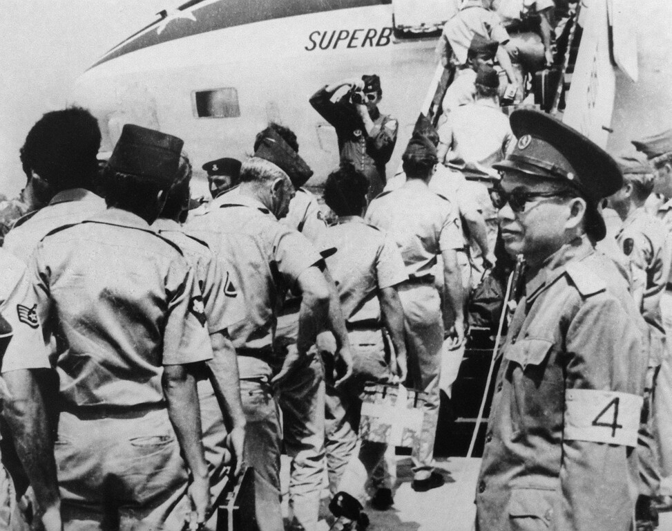 Description of . DA NANG, VIET NAM:  Photograph dated 1973 showing a North Vietnamese Army (NVA) officer (R) overseeing the departure of US military personnel at Da Nang airport, following the January 1973 signing of the Paris accords. (Photo credit should read AFP/Getty Images)