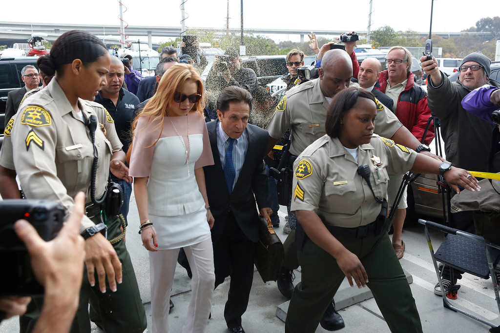 . Actress Lindsay Lohan is showered with gold glitter, second left, as she arrives with her attorney Mark Heller, for her trial Monday, March 18, 2013, at Los Angeles Superior court. Lohan is charged with three misdemeanor counts stemming from a crash on Pacific Coast Highway. She is charged with willfully resisting, obstructing or delaying an officer, providing false information to an officer and reckless driving. She is also accused of violating her probation in a misdemeanor jewelry theft case. (AP Photo/Damian Dovarganes)
