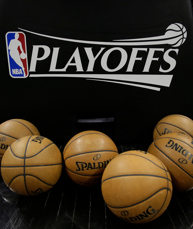 . A logo for the NBA playoffs and official basketballs are seen on the court prior to Game 1 of an NBA basketball playoffs basketball game between the Los Angeles Lakers and San Antonio Spurs, Sunday, April 21, 2013, in San Antonio, Texas. (AP Photo/Eric Gay)