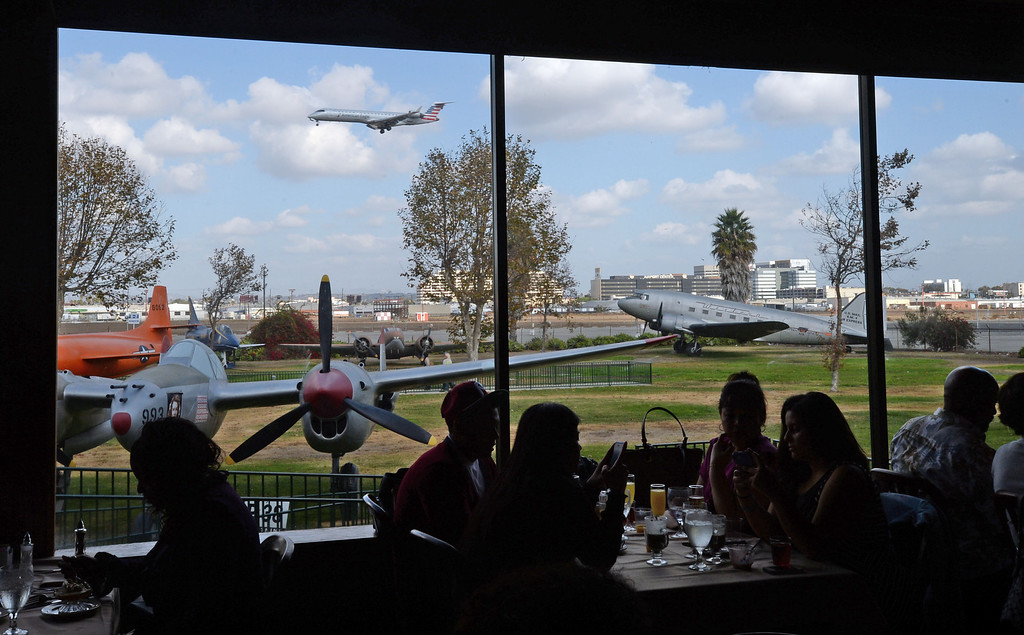 . People partake in Sunday brunch at the Proud Bird restaurant, which may be the last one, Sunday, November 17, 2013, in Los Angeles, CA.  The restaurant has been a fixture for almost 50 years but may close for good on November 21, unless a last minute deal can be made.  A plane lands past historical planes at the restaurant; with its unique location on LAX property and in the flightpath. Photo by Steve McCrank/DailyBreeze