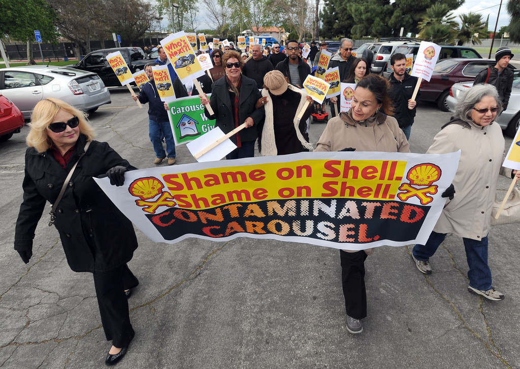 . Residents of the Carousel Tract neighborhood in Carson staged a protest against Shell Oil Friday by marching with signs from Dolphin Park to a Shell facility on Wilmington Avenue.  Myra Groce, left, and Clemencia Ortega, right, start the protest out of the park while carrying their banner. 20130308 Photo by Steve McCrank / Staff Photographer