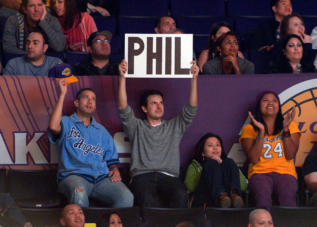 . A fan holds up a sign for Phil Jackson during the second half of the Los Angeles Lakers\' NBA basketball game against the Golden State Warriors, Friday, Nov. 9, 2012, in Los Angeles. Bernie Bickerstaff is sitting in as head coach while the Lakers search for a replacement for Mike Brown who was fired earlier Friday. The Lakers won 101-77. (AP Photo/Mark J. Terrill)