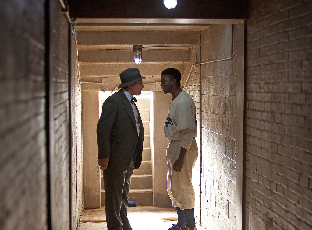 Description of . This film image released by Warner Bros. Pictures shows Chadwick Boseman as Jackie Robinson, right, and Harrison Ford as Branch Rickey in a scene from