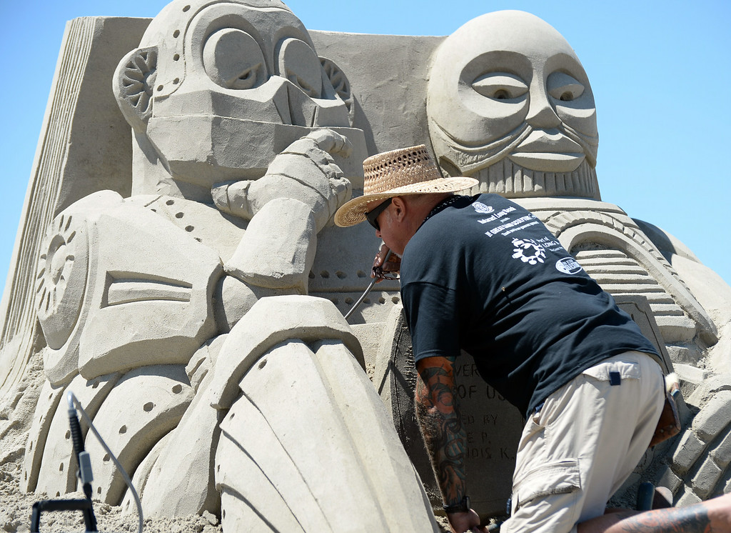 . Artists took to the beach at Belmont Shore for the 82nd Annual Sand Sculpture Contest Saturday, August 16, 2014, Long Beach, CA.  Bruce Phillips blows air threw a straw as he intricately details his sculpture. Photo by Steve McCrank/Daily Breeze